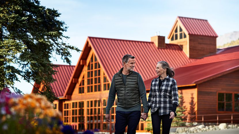 A couple strolls in front of Denali Princess Wilderness Lodge.