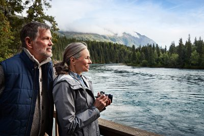 A couple overlooks the river at Kenai Princess Wilderness Lodge