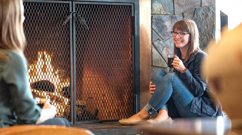 A woman sips coffee in front of a fireplace while talking to another woman.